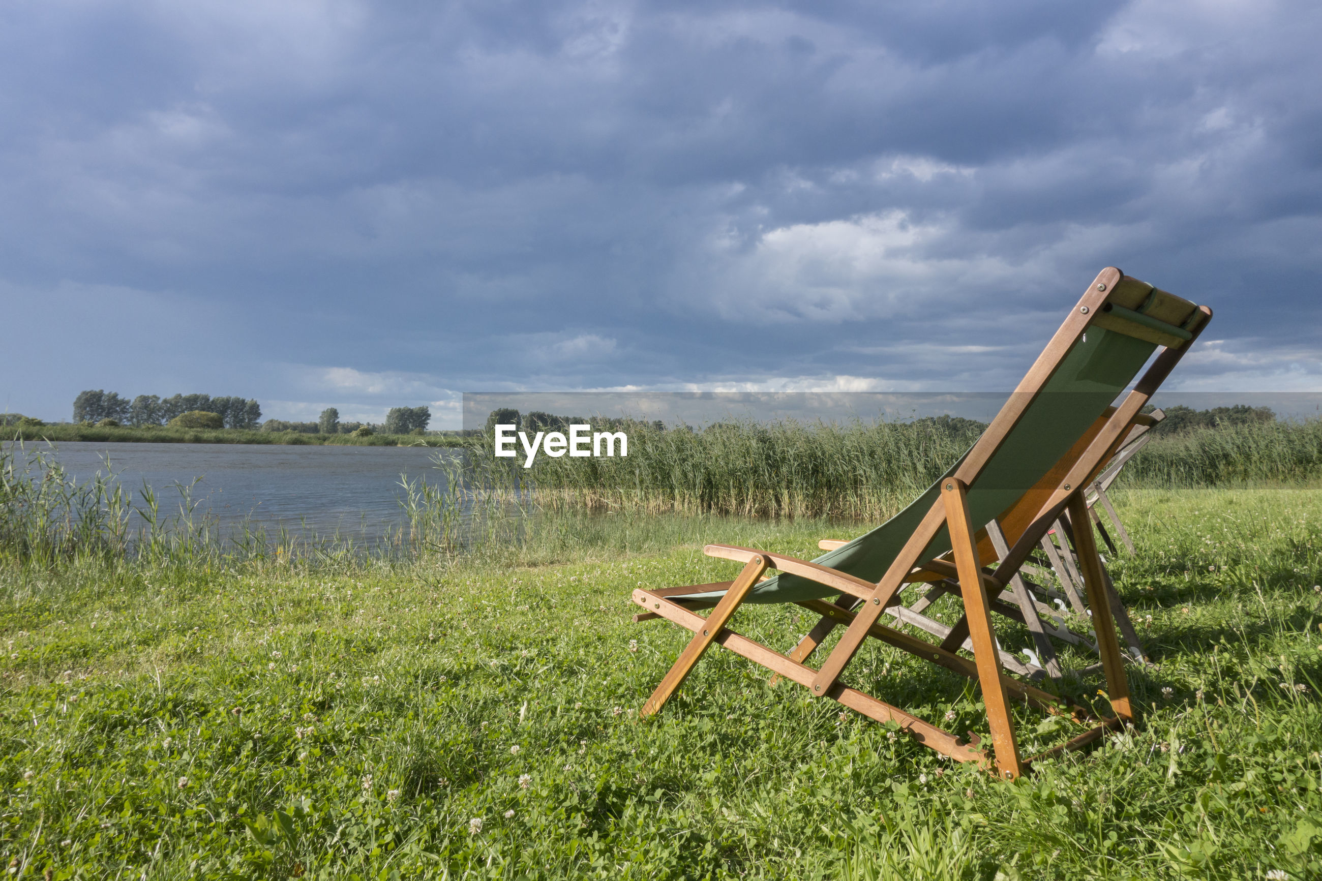 VIEW OF CHAIRS ON GRASSY FIELD AGAINST SKY
