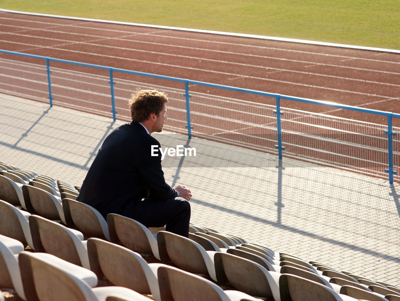 sitting, one person, seat, real people, sport, day, adult, men, sunlight, males, nature, business person, businessman, side view, full length, looking, three quarter length, business, contemplation, waiting