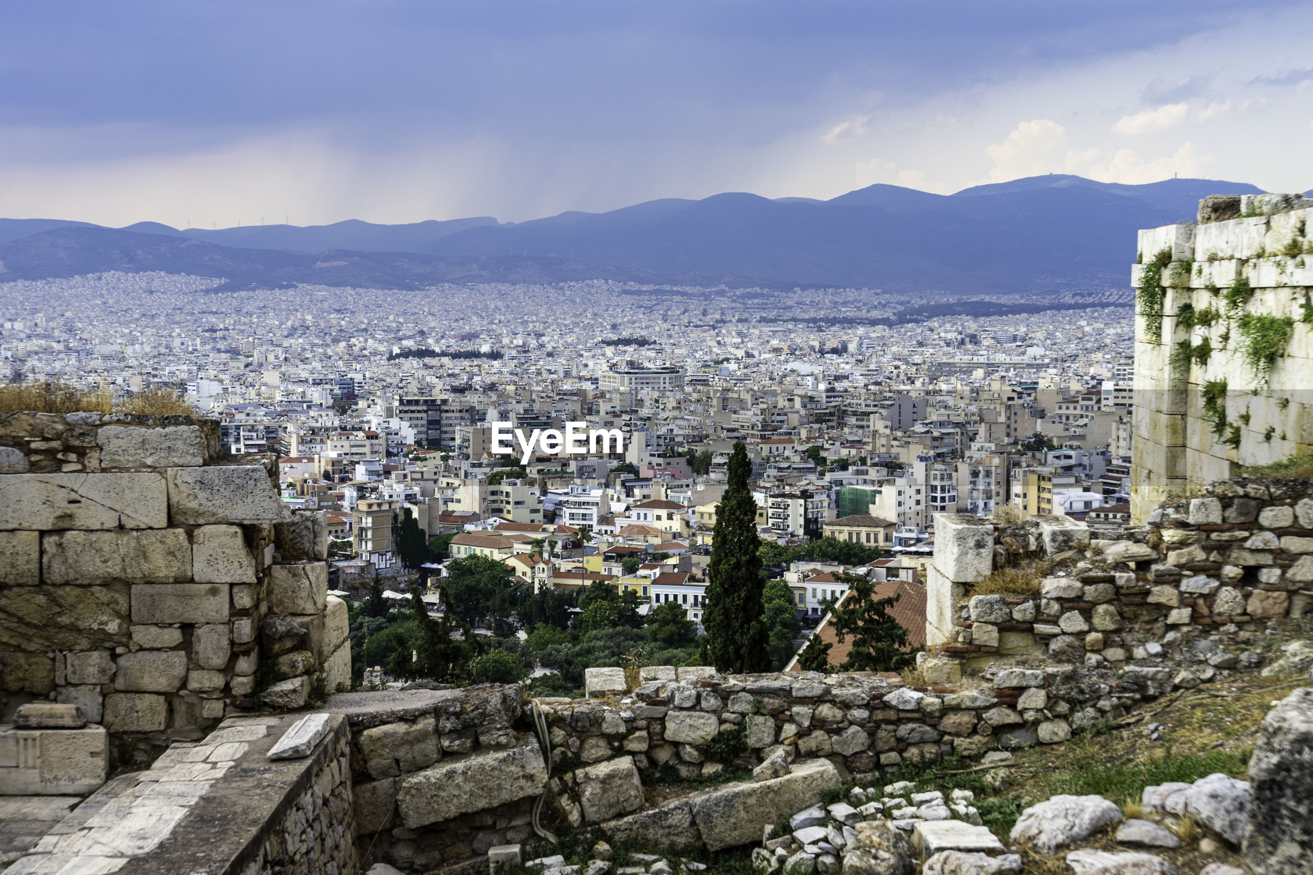 View from acropolis over city of athens in front of rain clouds