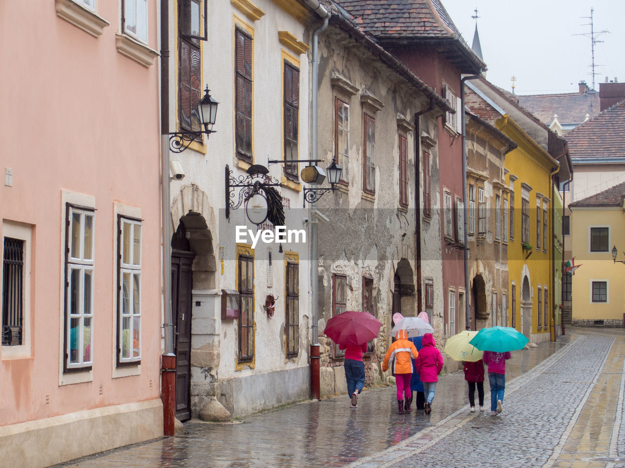 building exterior, architecture, walking, built structure, rear view, outdoors, street, residential building, the way forward, real people, day, wet, city, alley, men, full length, women, togetherness, adult, people