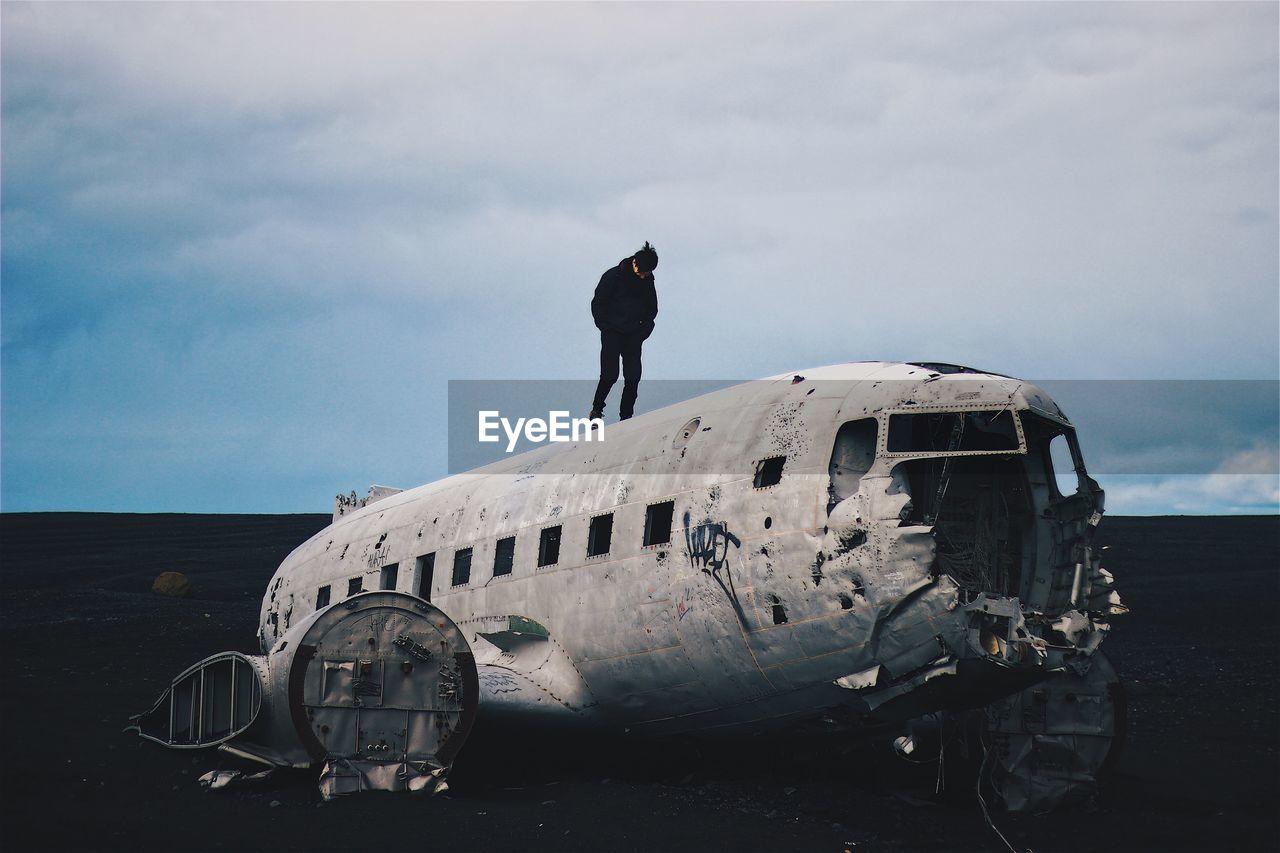 Man Standing On Solheimasandur Plane Wreck At Black Sand Beach Against Sky