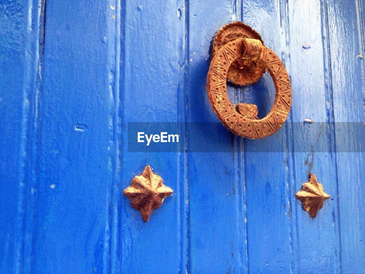 Brown Doorknob Handing On Blue Door