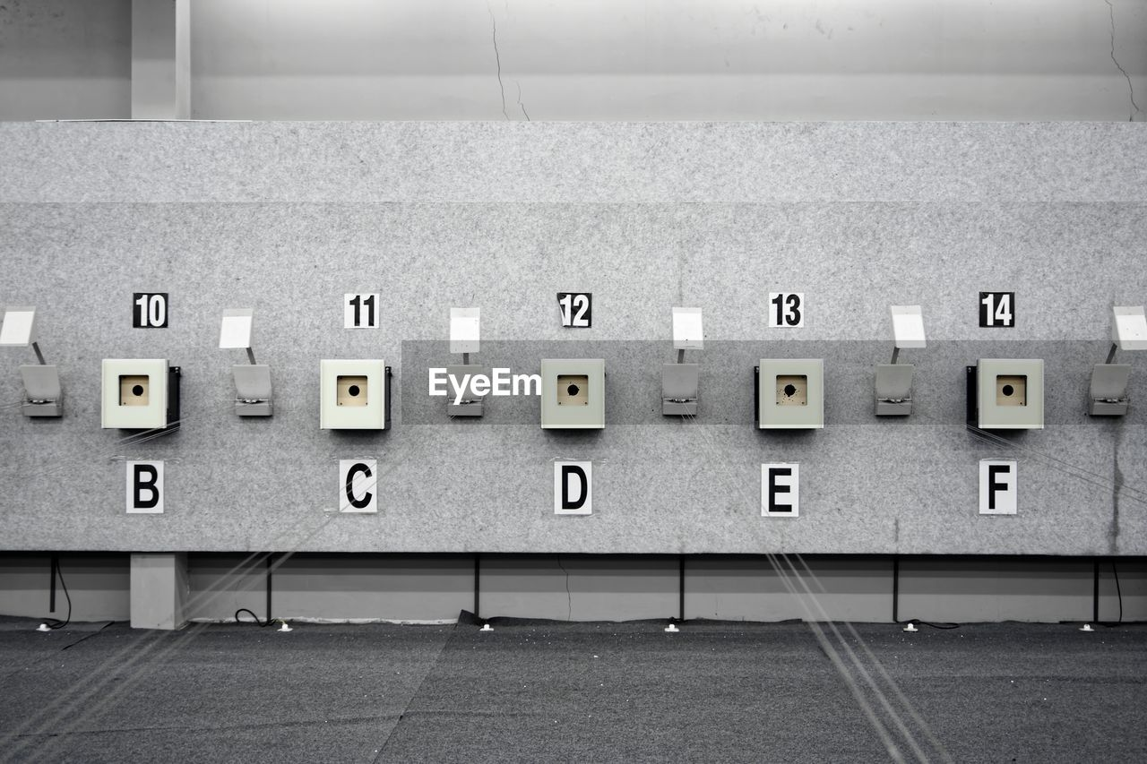 no people, electricity, technology, wall - building feature, power supply, in a row, indoors, side by side, number, connection, repetition, absence, letter, fuel and power generation, control, communication, architecture, push button, wall, electrical component