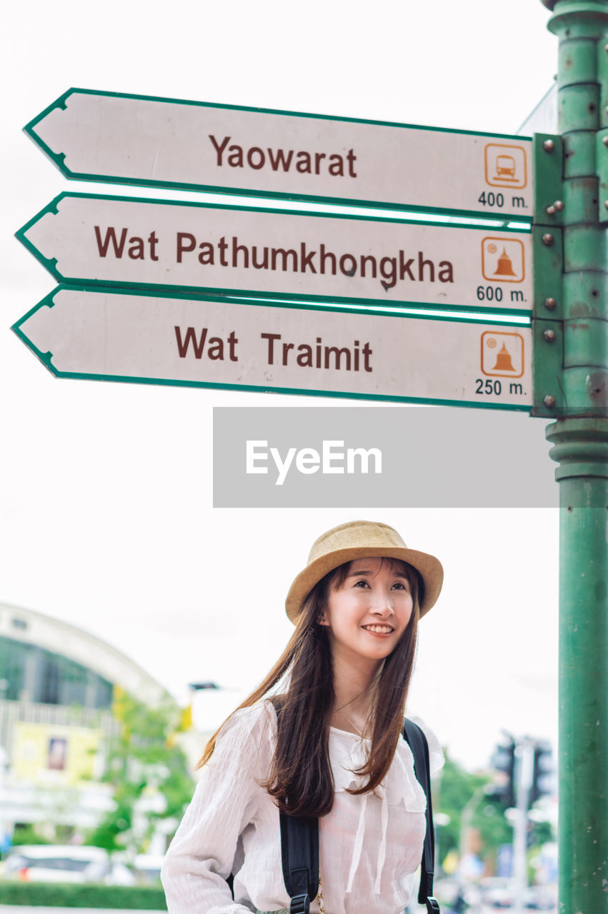text, one person, portrait, western script, young adult, smiling, communication, clothing, script, hat, standing, non-western script, day, lifestyles, looking at camera, sign, real people, casual clothing, focus on foreground, guidance, hairstyle, beautiful woman