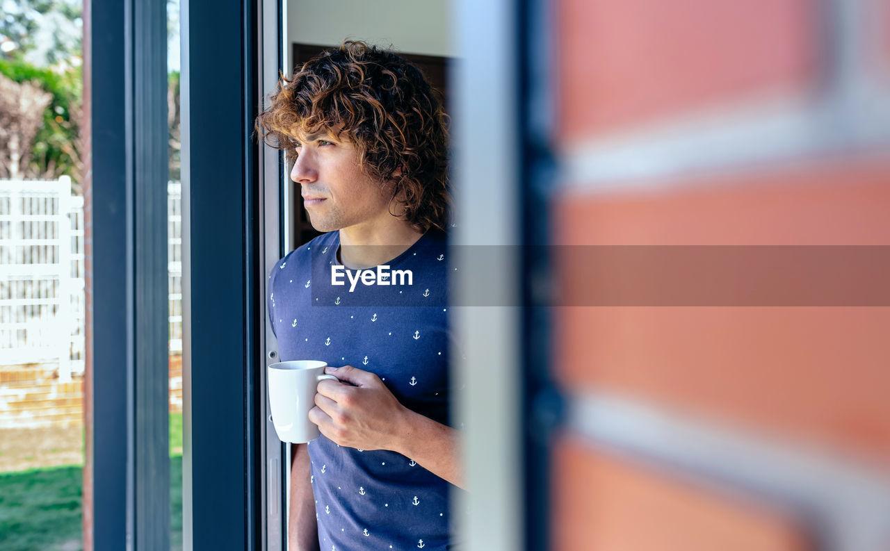 Man having coffee while standing at doorway