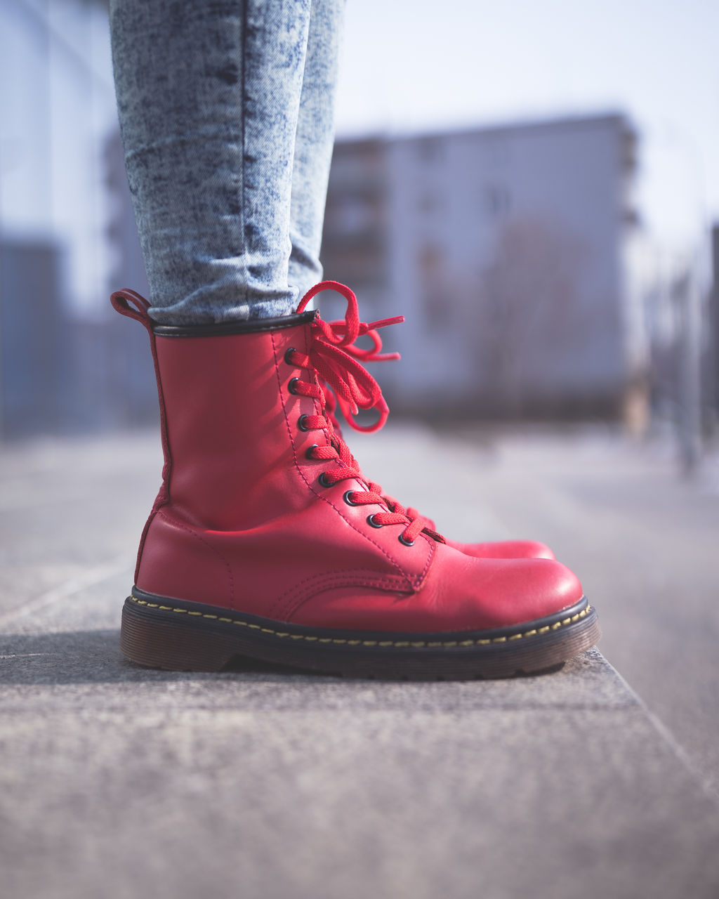 shoe, low section, one person, human leg, red, body part, real people, human body part, close-up, selective focus, shoelace, day, lifestyles, jeans, unrecognizable person, focus on foreground, standing, outdoors, limb, human foot, human limb, leather, lace - fastener