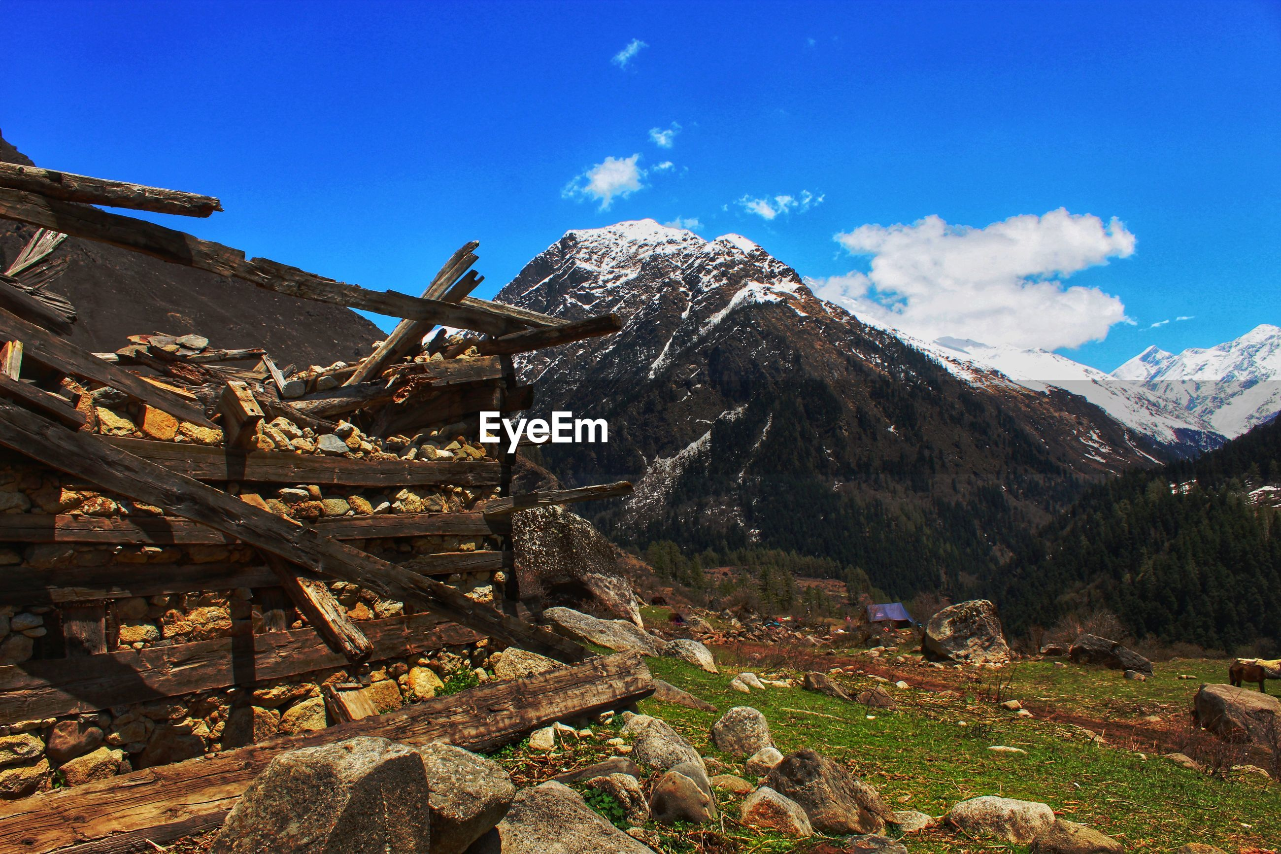 Scenic view of ruined hut with snowcapped mountains against blue sky
