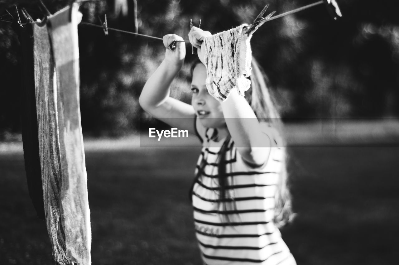 Girl Holding Clothesline While Standing In Yard