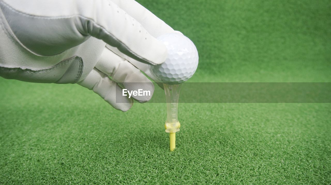 Cropped hand of person keeping golf ball on tee
