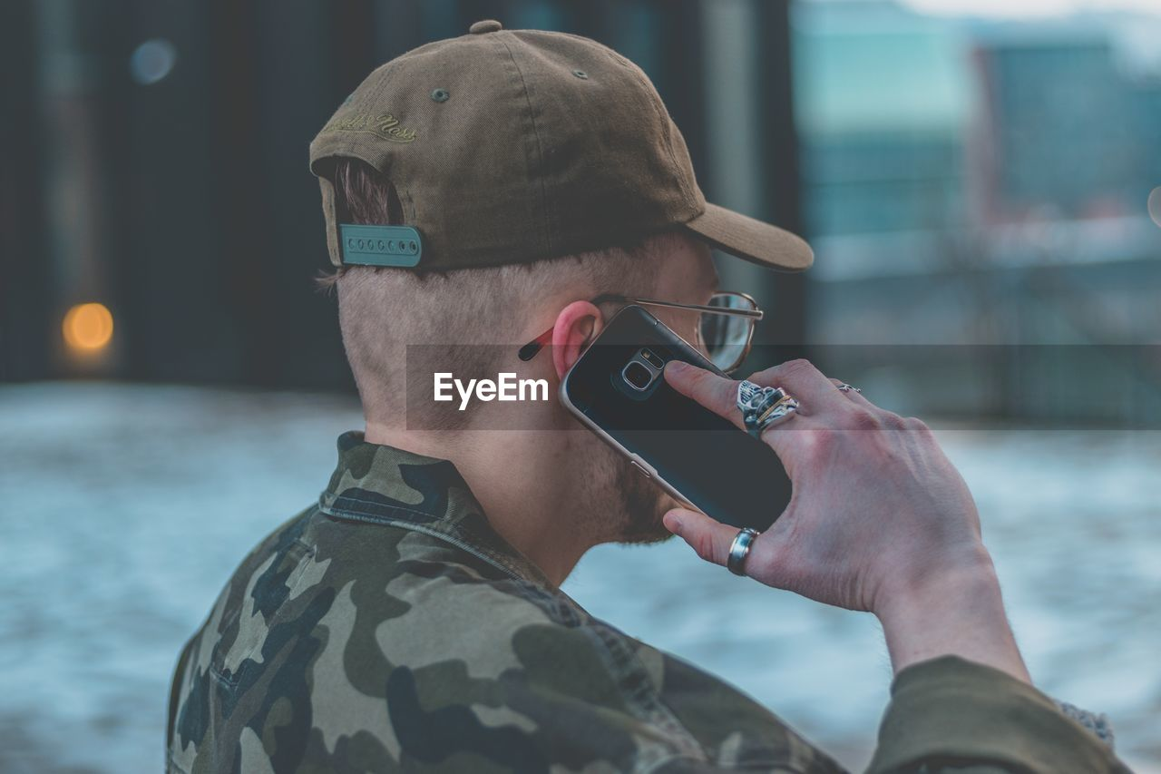 headshot, focus on foreground, men, military, one person, real people, technology, military uniform, holding, army, close-up, leisure activity, army soldier, outdoors, day, water, camouflage clothing, young adult, people
