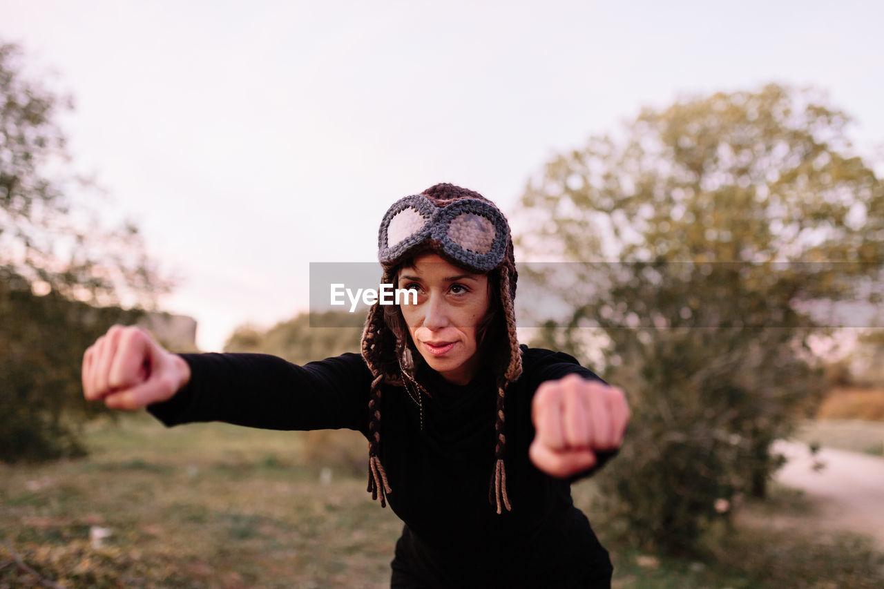Woman wearing knit hat exercising at park