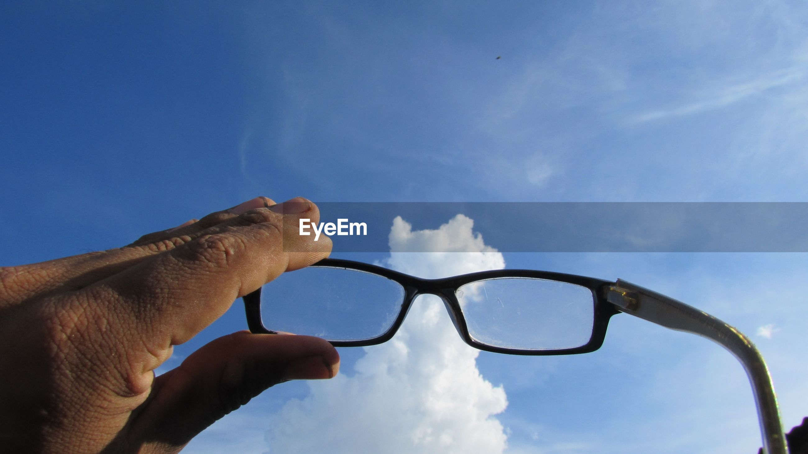 Cropped hand holding eyeglasses against blue sky