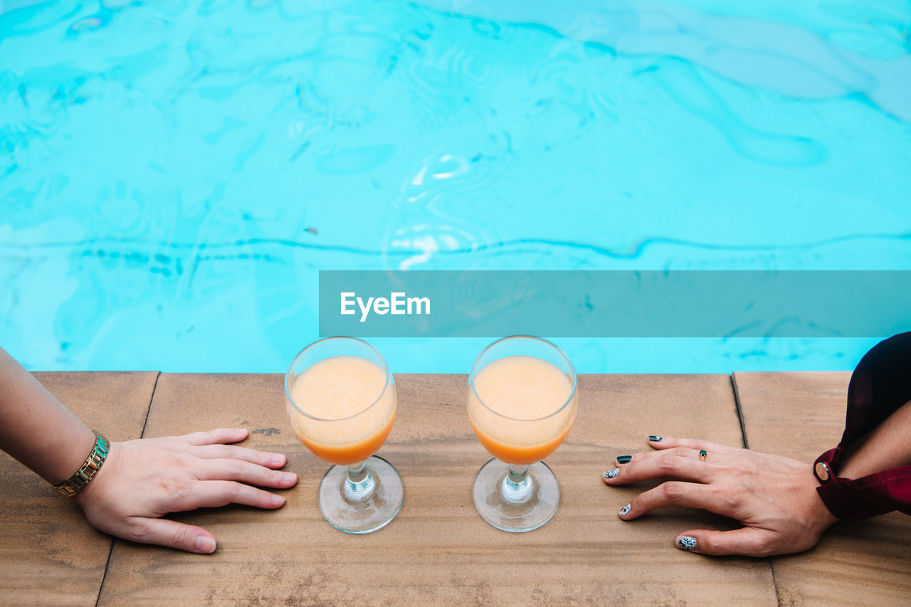 Cropped hands of women by juice against swimming pool