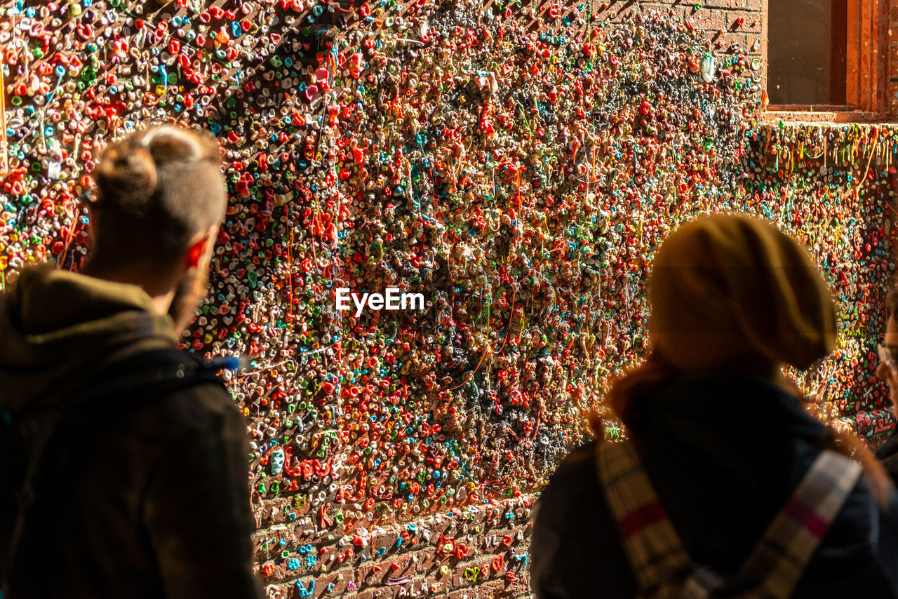 Rear view of people looking at gum wall