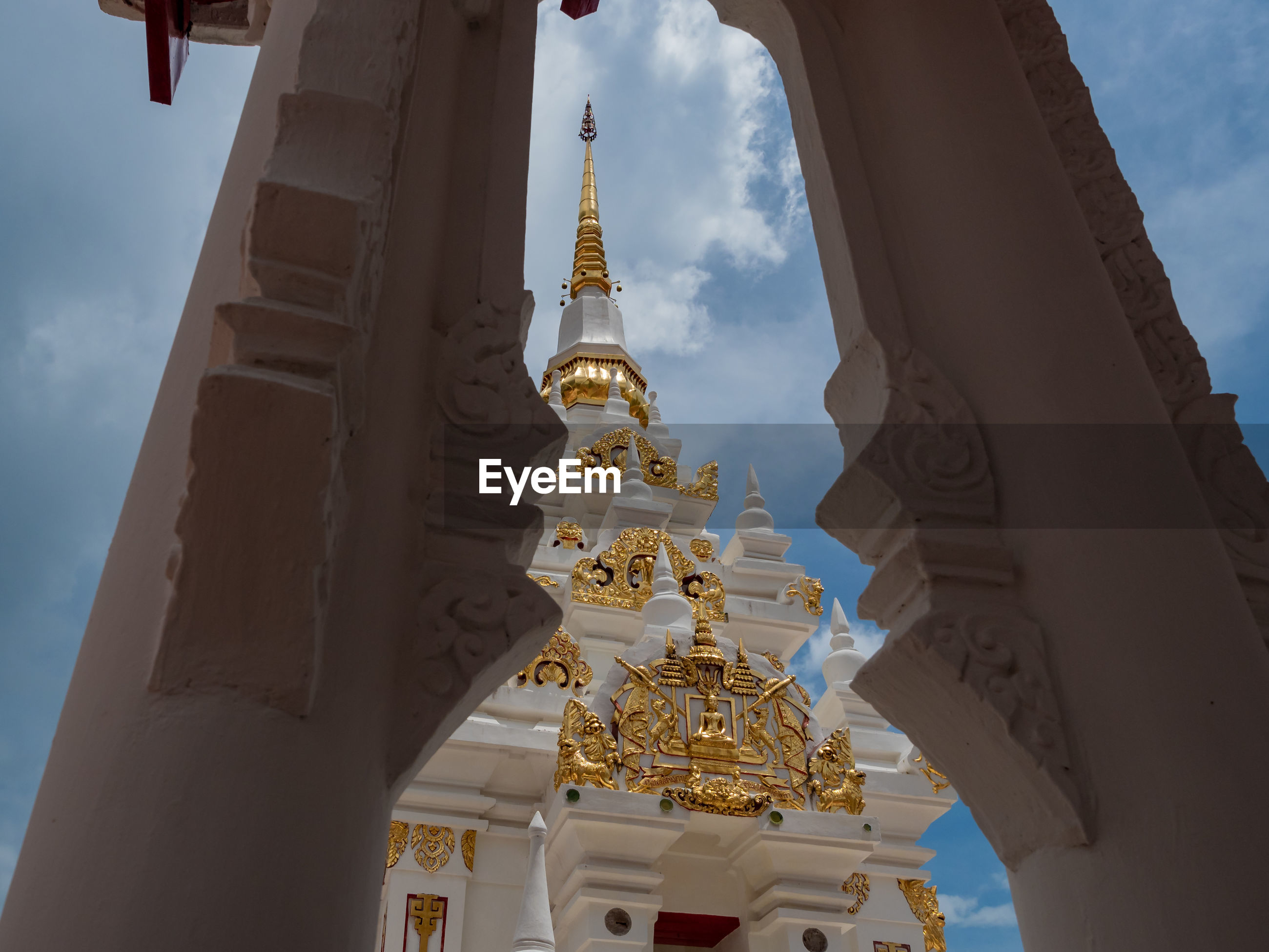 Thai traditional style white pagoda inside the temple with blue sky background.