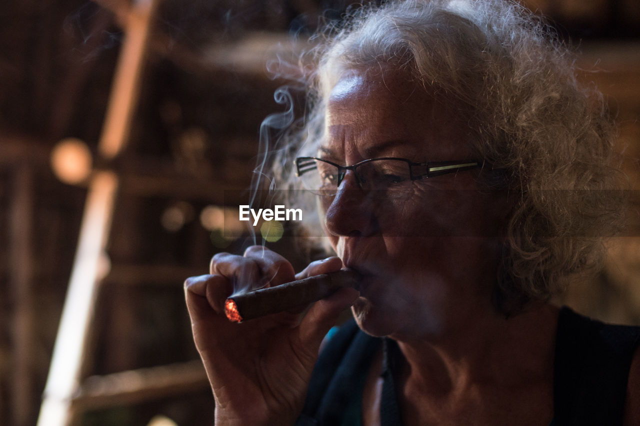 Close-Up Portrait Of A Old Woman Smoking Cigar