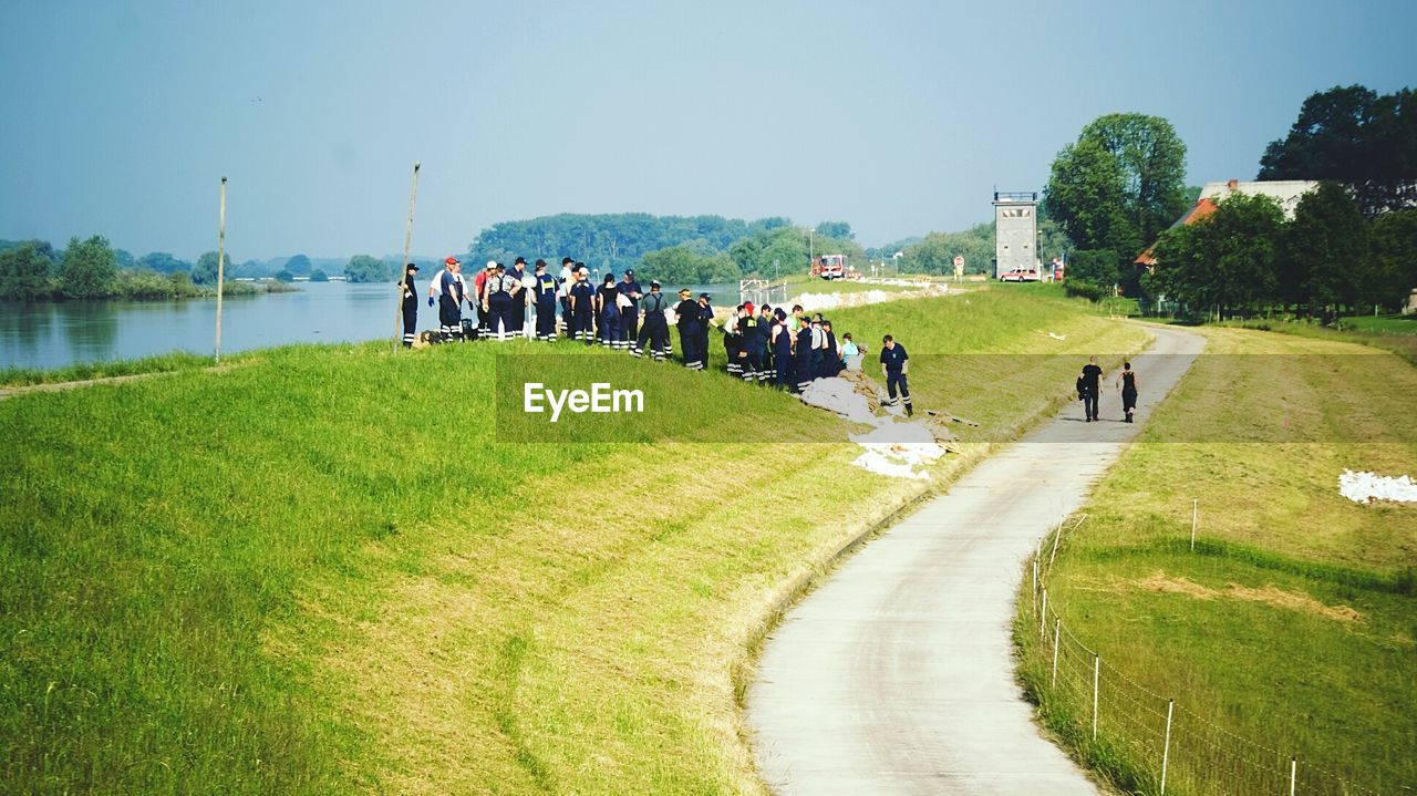 People standing in grassy field by river against clear sky