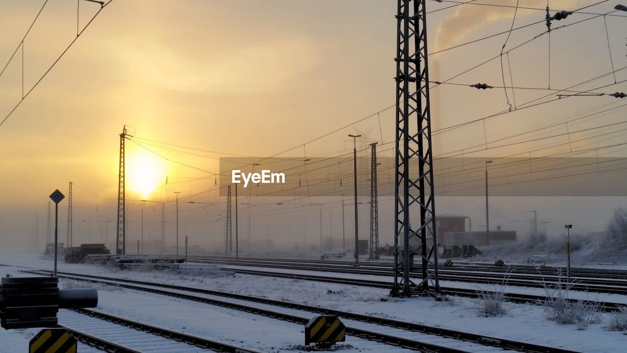 winter, snow, cold temperature, weather, cable, rail transportation, connection, transportation, railroad track, sunset, nature, electricity pylon, power line, sky, no people, field, outdoors, technology, beauty in nature, day