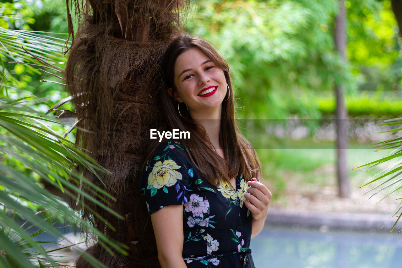 PORTRAIT OF SMILING YOUNG WOMAN AGAINST TREES
