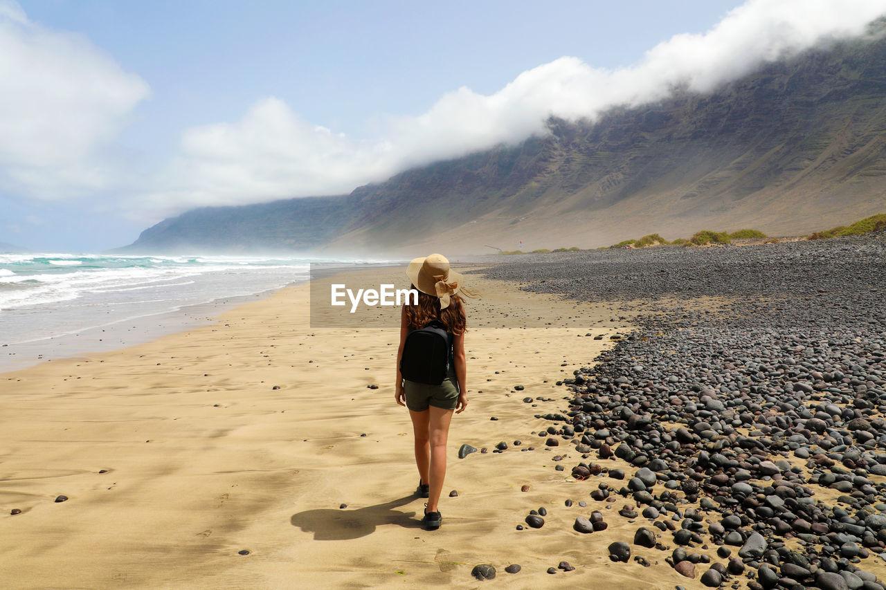 Rear View Full Length Of Woman Walking At Beach