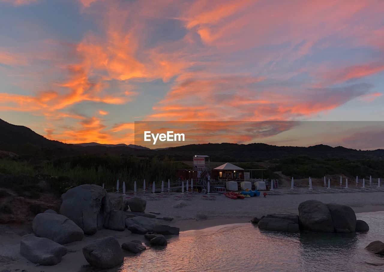 sky, cloud - sky, sunset, rock, solid, beauty in nature, rock - object, water, nature, scenics - nature, land, beach, mountain, architecture, tranquility, orange color, built structure, tranquil scene, sea, no people, outdoors