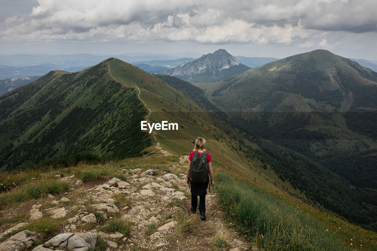 REAR VIEW OF MAN LOOKING AT MOUNTAIN RANGE AGAINST SKY