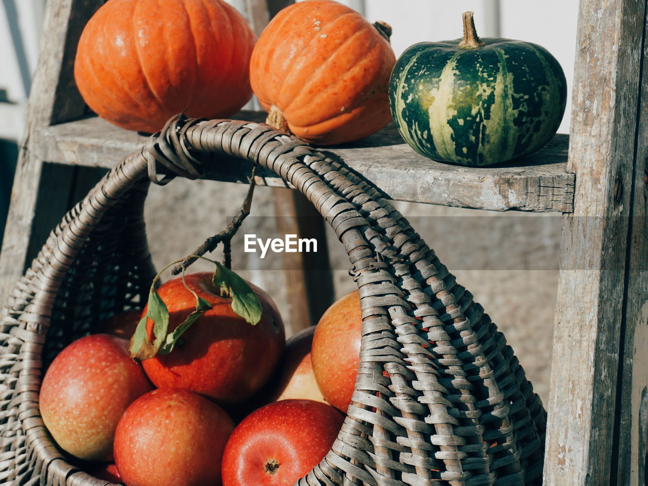 Close-Up Of Apples In Basket With Pumpkin On Table