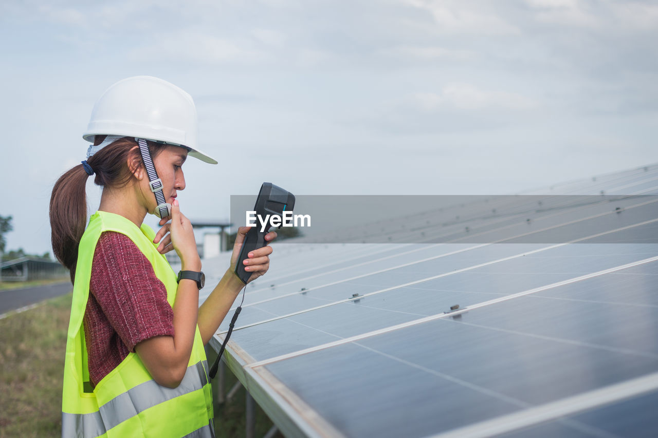 technology, sky, real people, hat, alternative energy, fuel and power generation, renewable energy, one person, environmental conservation, solar energy, solar panel, environment, adult, wireless technology, nature, communication, holding, lifestyles, occupation, day, outdoors, sustainable resources