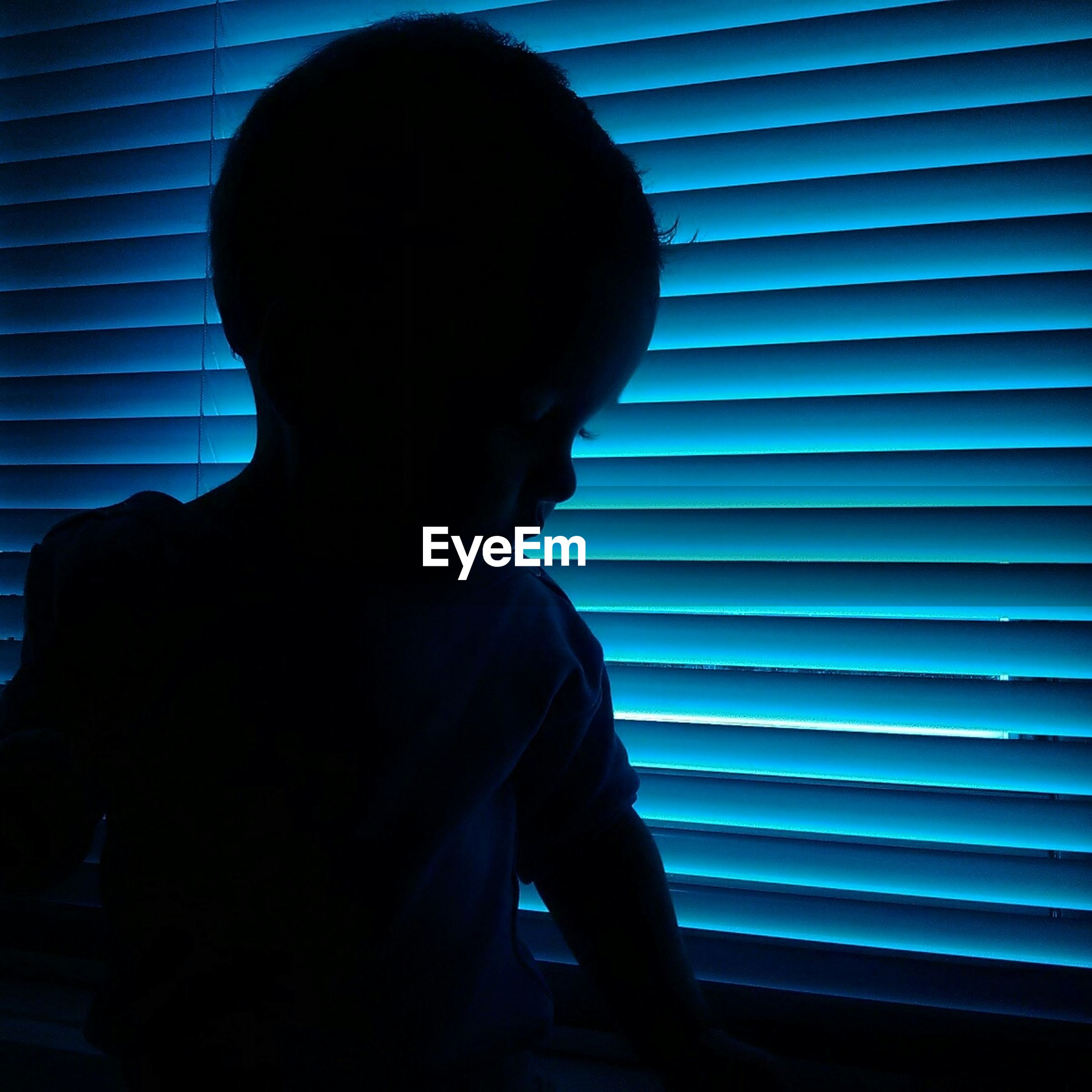 Baby sitting by blue blinds