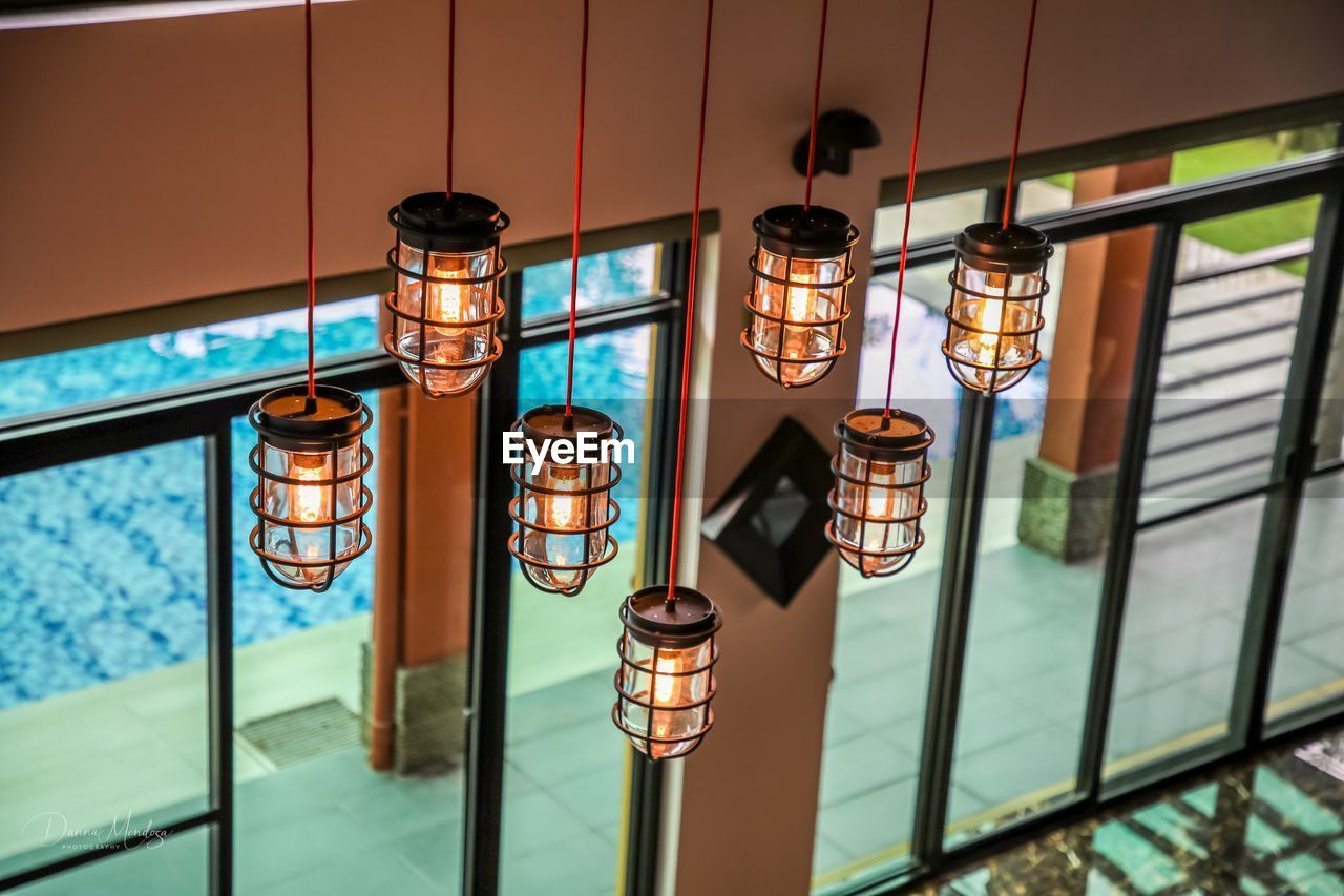 lighting equipment, illuminated, focus on foreground, glass - material, no people, transparent, indoors, glowing, electric lamp, close-up, window, day, electricity, built structure, architecture, railing, electric light, nature, metal, ceiling