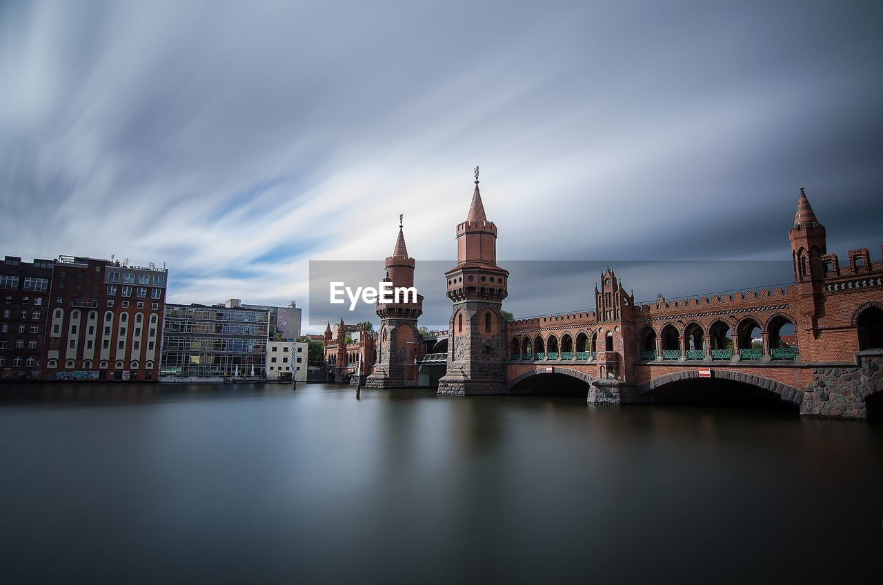 Oberbaumbrucke Over Spree River Against Cloudy Sky