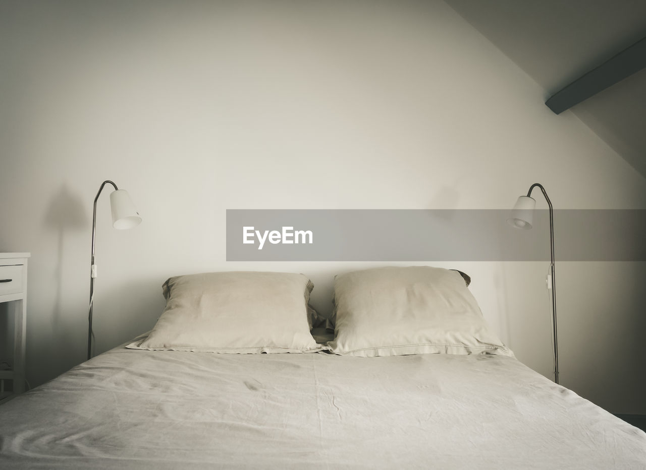 Empty bed against white wall at home