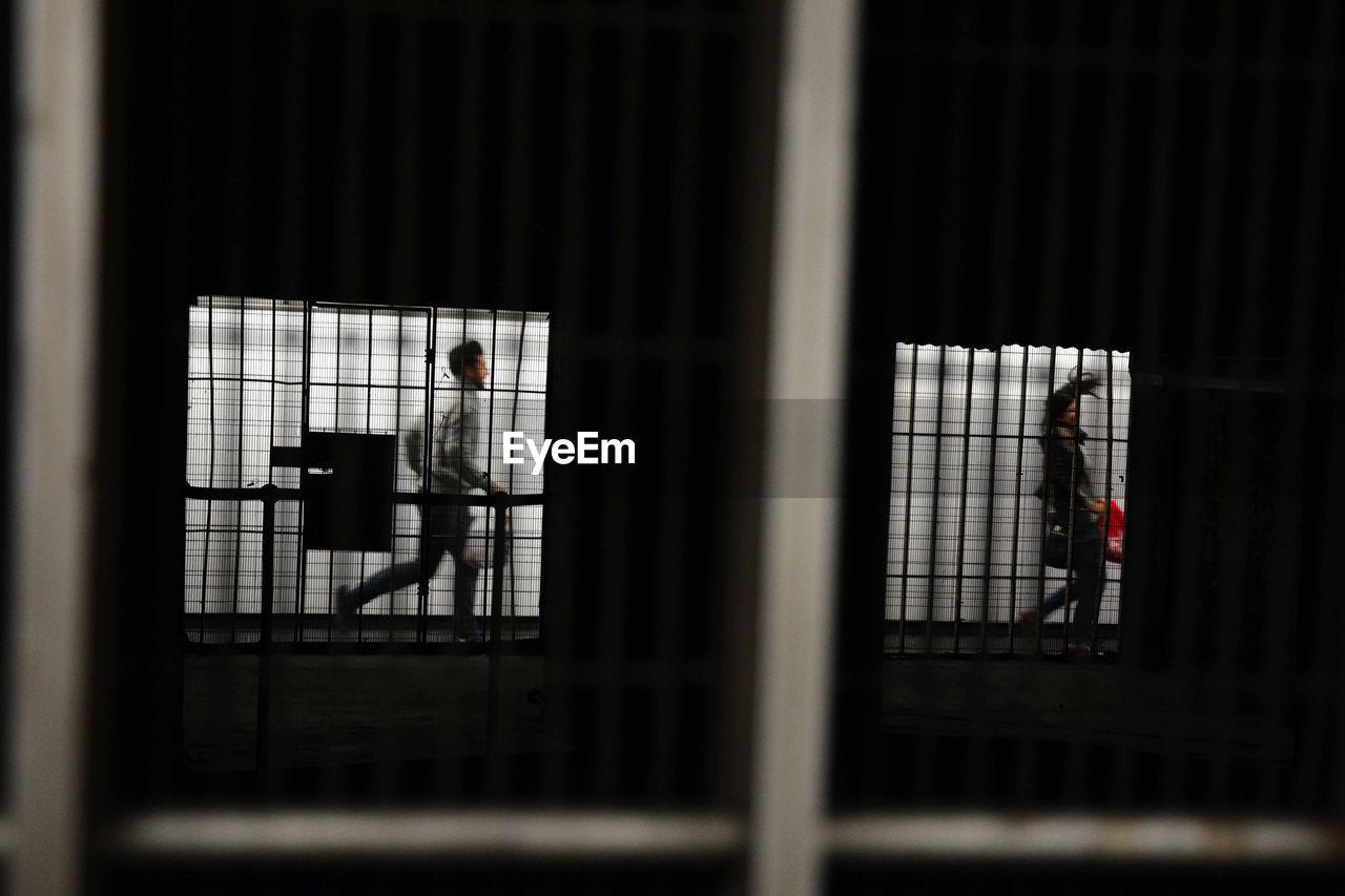 People running in corridor seen through window