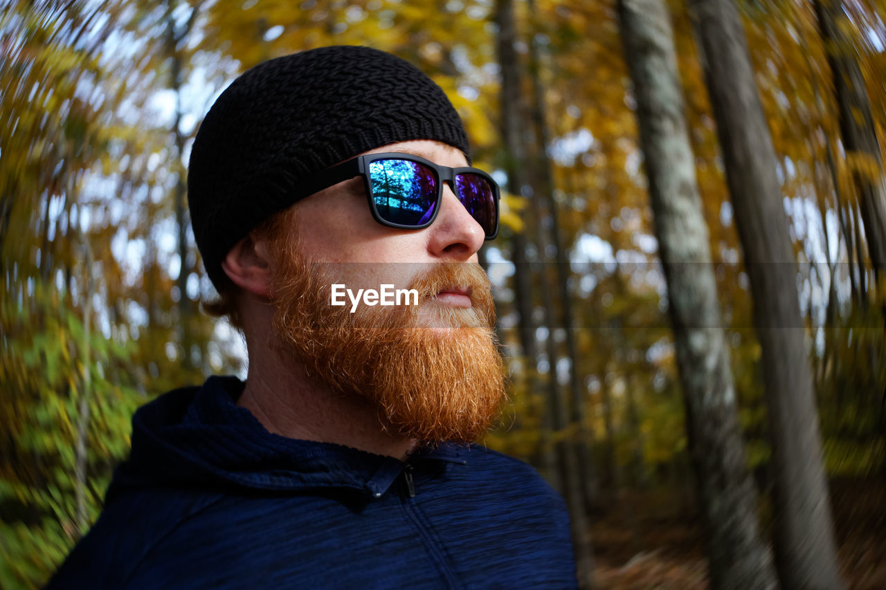 Bearded man wearing sunglasses and knit hat against trees