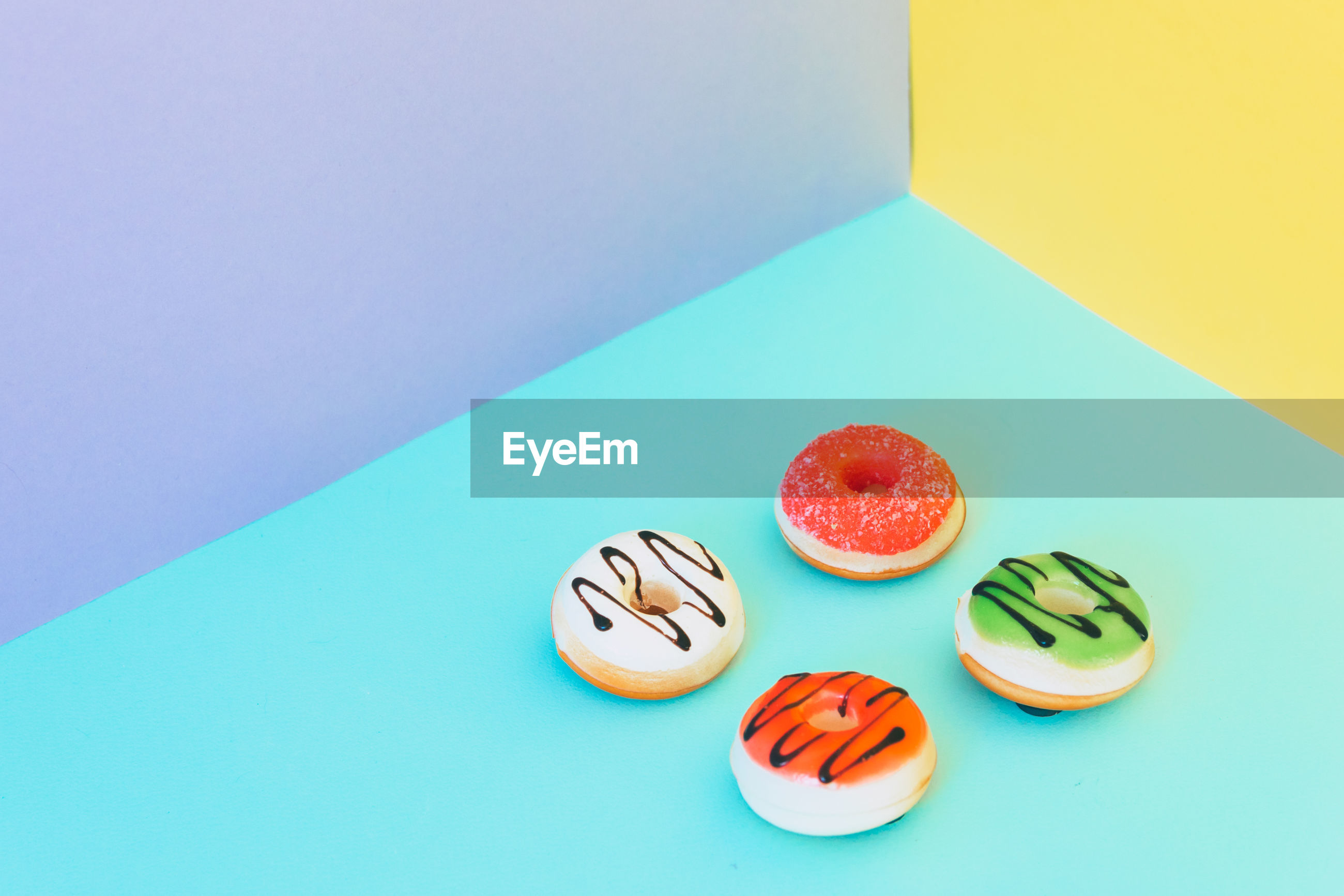 High angle view of donuts against colored background