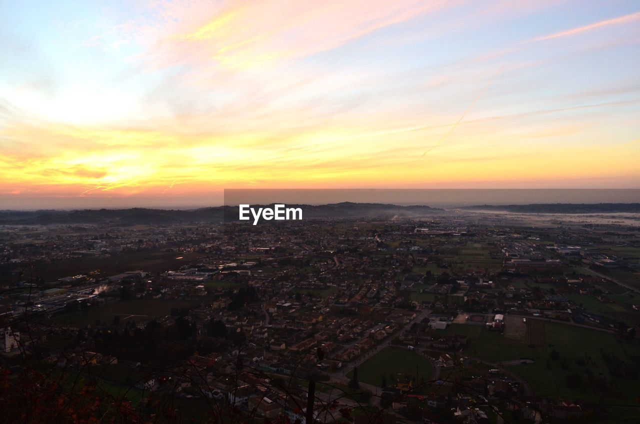 Ariel view of cityscape against cloudy sky during sunset