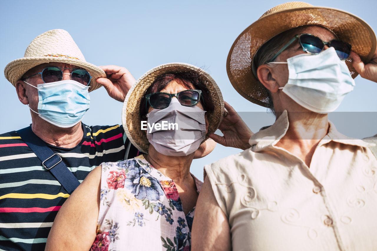 Portrait of senior people wearing hat standing against sky
