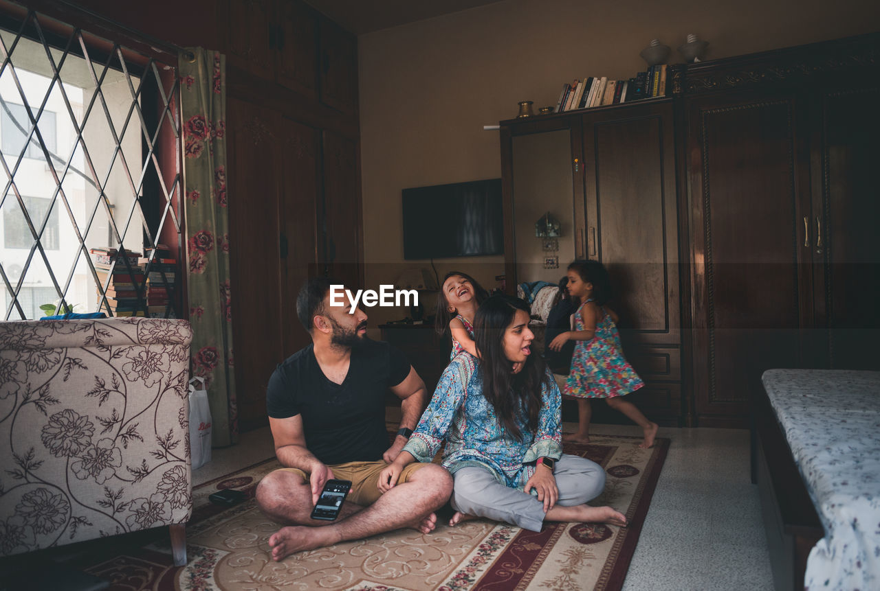 Parents with daughters on carpet in living room at home