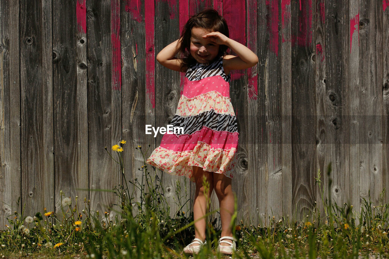 Full length portrait of smiling girl standing in yard against wooden fence