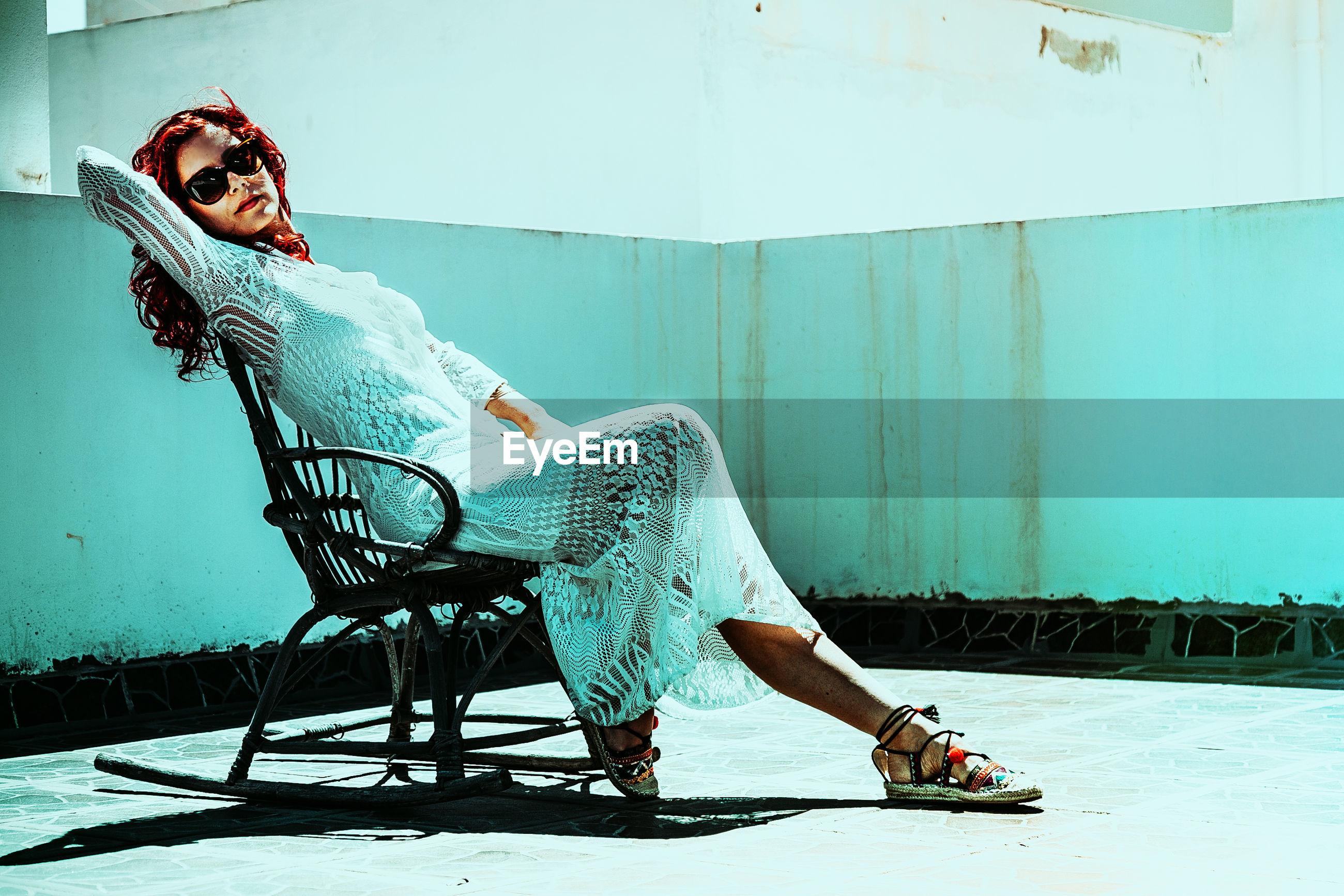 Portrait of beautiful woman sitting on rocking chair