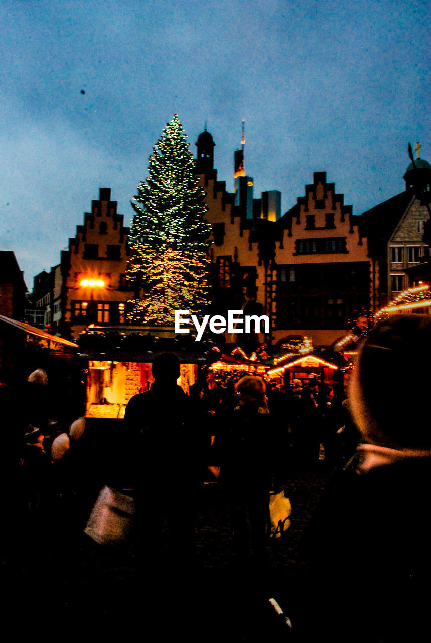 architecture, building exterior, real people, built structure, night, tree, illuminated, large group of people, men, sky, city, celebration, leisure activity, lifestyles, outdoors, women, togetherness, crowd, people