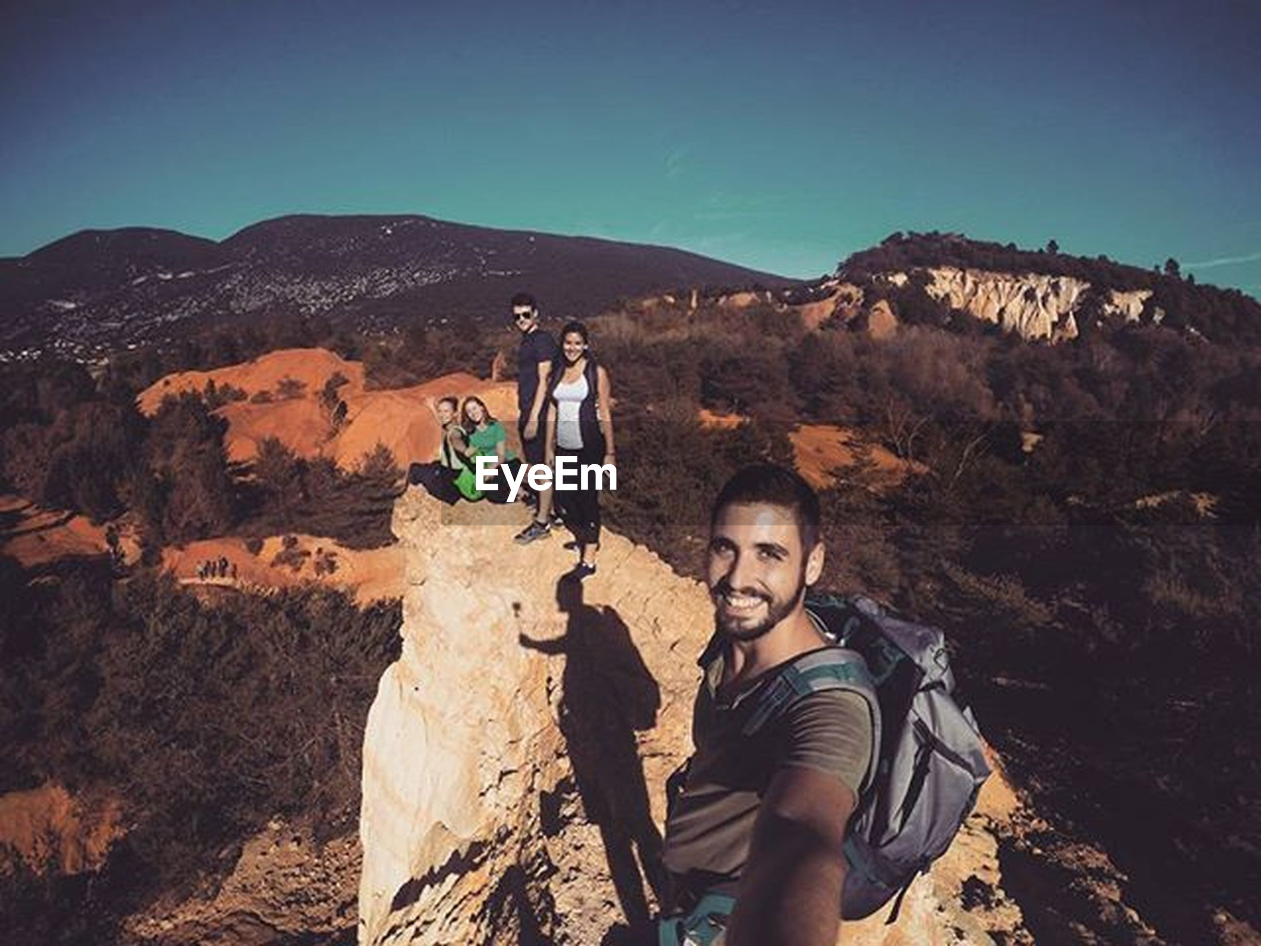 lifestyles, mountain, leisure activity, holding, casual clothing, clear sky, rock - object, men, standing, sky, blue, sunlight, nature, mountain range, person, rock formation, photographing, rear view