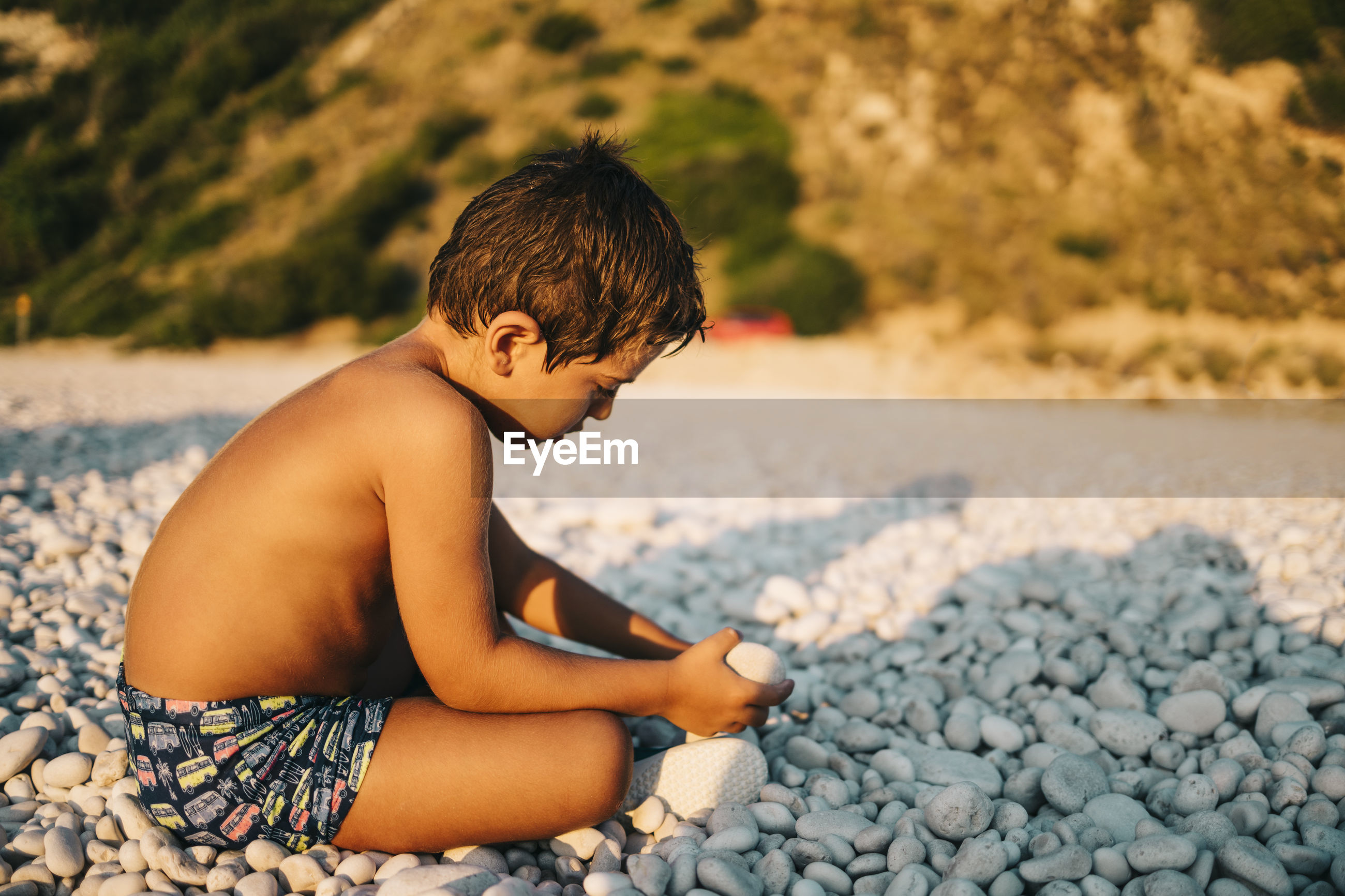 Side view of shirtless boy sitting on pebble