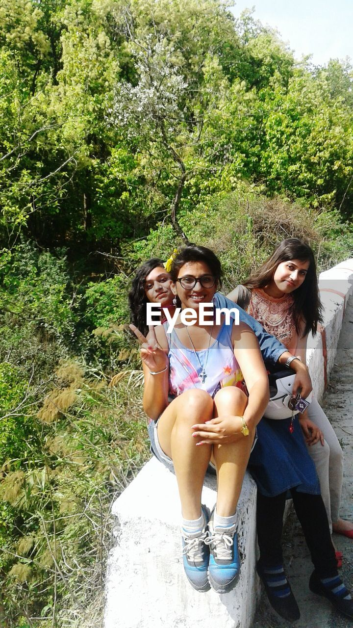 Portrait Of Smiling Female Friends Sitting On Retaining Wall By Trees