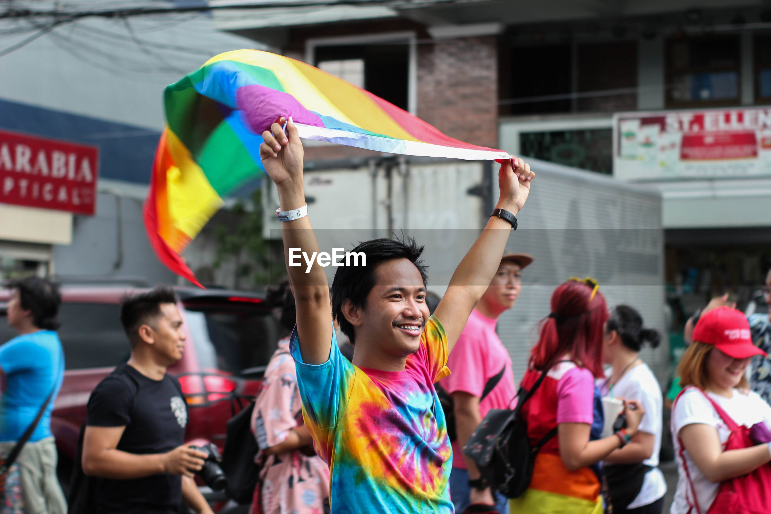 Smiling man holding rainbow flag while standing in city