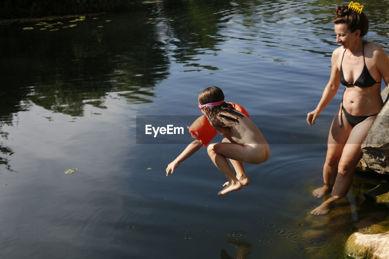 REAR VIEW OF TWO BOYS IN LAKE