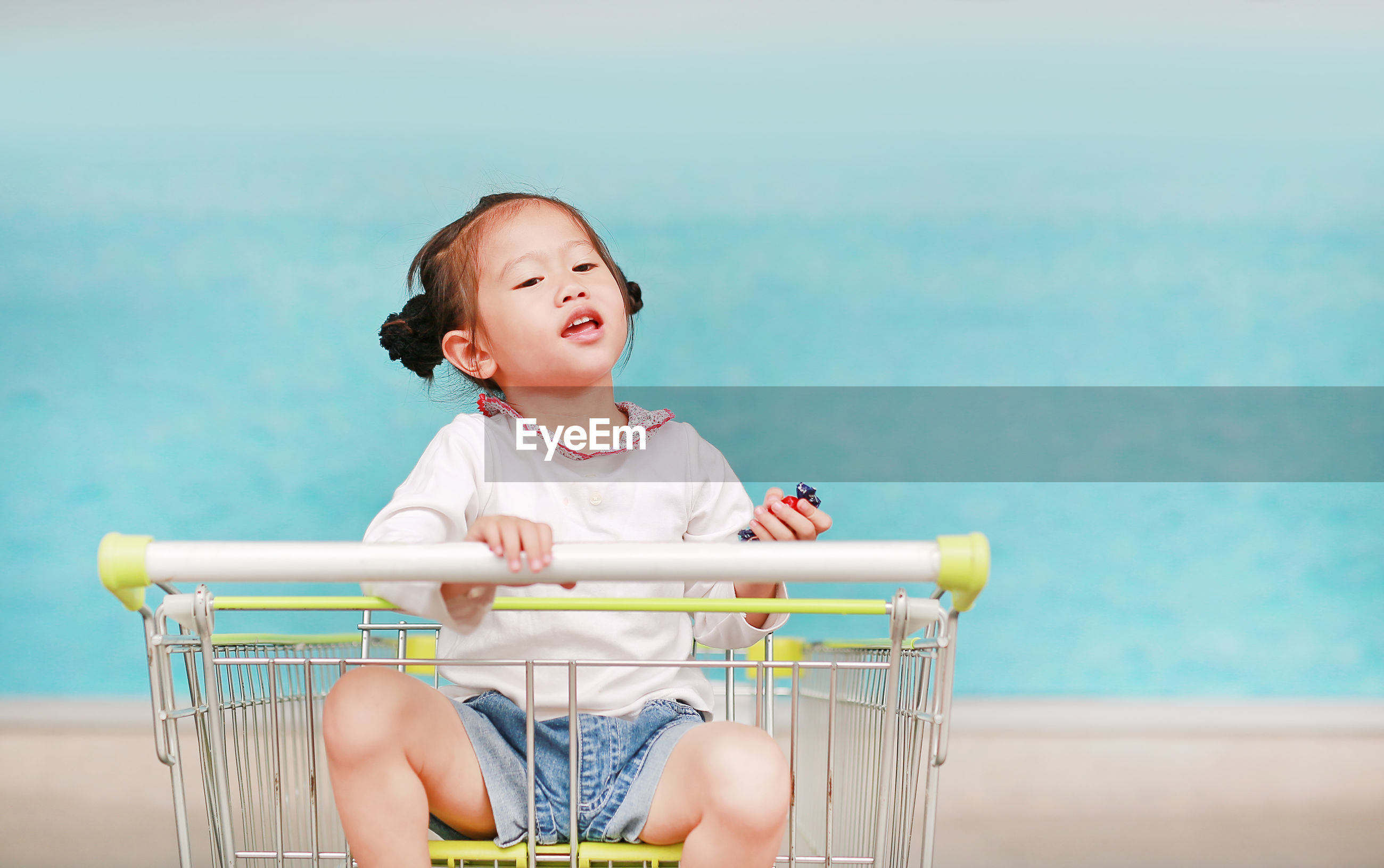 Cute girl sitting in shopping cart against wall