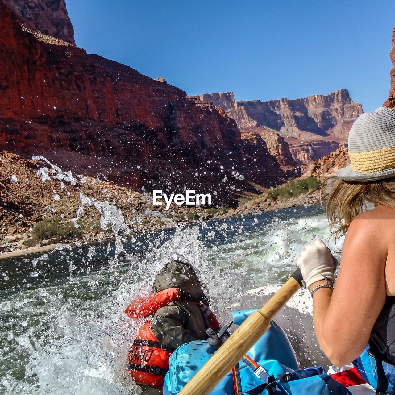 Close-up of woman rafting in river by grand canyon