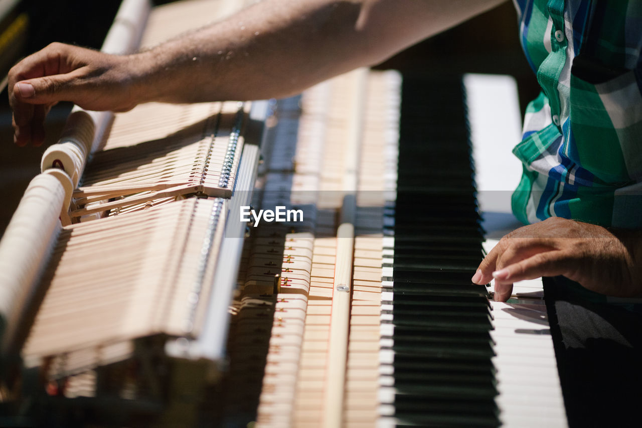Midsection Of Pianist Playing Piano