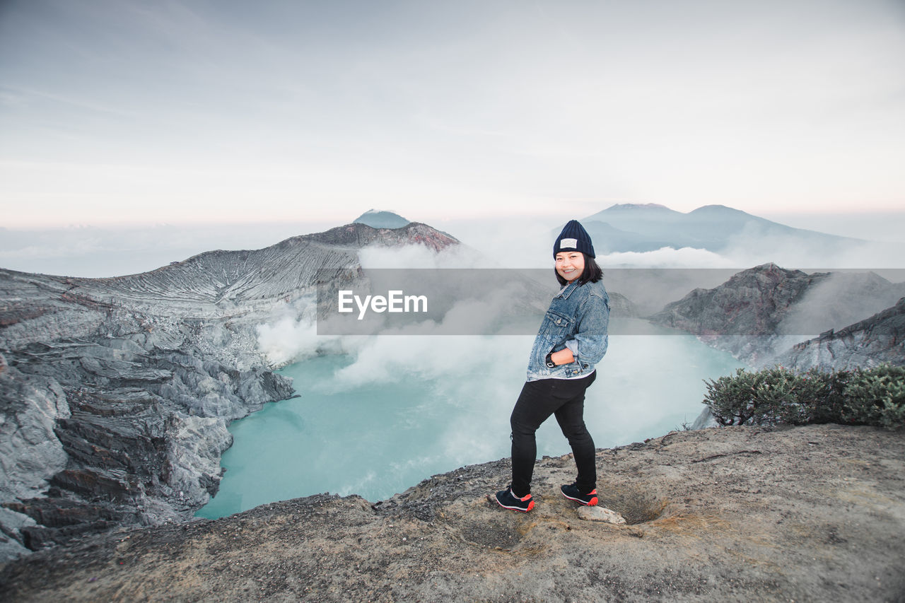 Full Length Portrait Of Woman Standing On Mountain